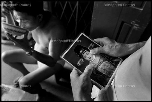 США, Нью-Йорк. 1998. Иммигрнат смотрит на фото сына, с которым он уже не виделся 5 лет.