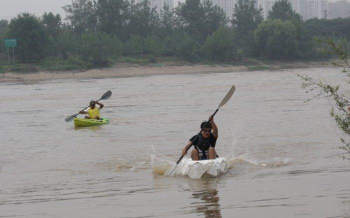 Уханьский студент Ван Луяо переплывает реку Ханьцзян на сконструированной им лодке из бумаги. Сзади слева: подстраховка на каноэ.