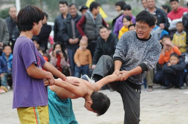 Китайский уличный цирк выламывает и душит детей в своих выступлениях