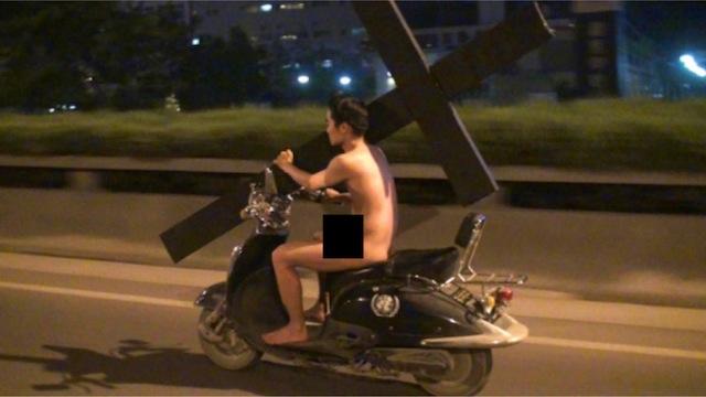 Фото: Голый китаец проехался по Пекину на скутере с огромным крестом