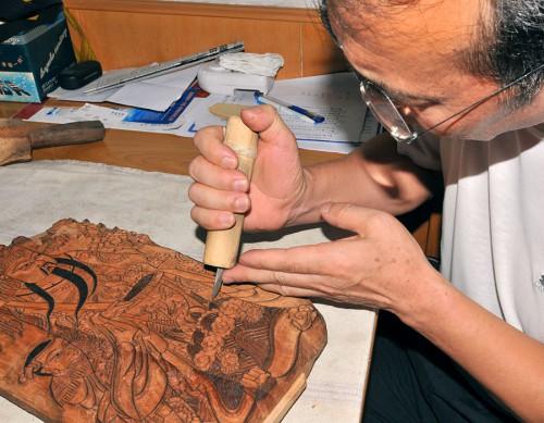 Работающий в традиционной манере мастер-резчик изготавливает деревянную печатную доску, оттиск с которой и будет няньхуа.