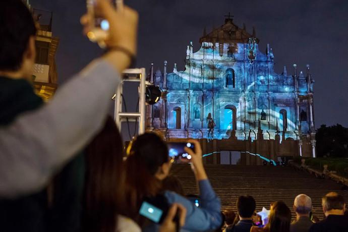 Зрители фотографируют светопредставление в день открытия Фестиваля света в Макао. Источник: Zhang Jinjia / Xinhua