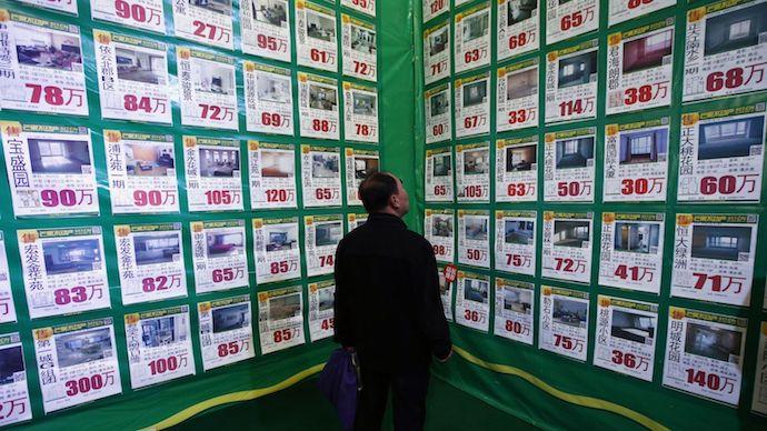 Мужчина изучает предложения на рынке вторичного жилья: 50万 - это 4,5 млн рублей. Источник: Enterprise Innovation