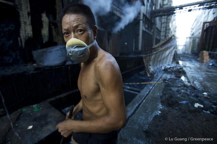 Работник фабрики собирает камни после стирки джинсов. Источник: greenpeace
