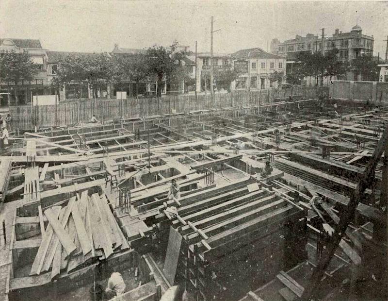 Здания во время строительства; на фоне видна Bubbling Well Road , нынешняя West Nanjing Road. Источник: The Builder 中国建筑 (1933)