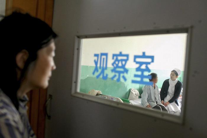 Пациент смотрит на медсестру, беседующую с другим пациентом в психиатрической клинике в Аньшани, провинция Ляонин. 9 мая 2014 года. Источник: VCG