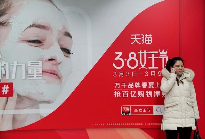"""Девушка стоит на фоне рекламного плаката распродажи по случаю """"Дня королевы"""" - 女王节. Источник: Báo Mới"""